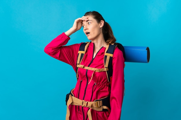 Young mountaineer woman over isolated blue wall doing surprise gesture while looking to the side