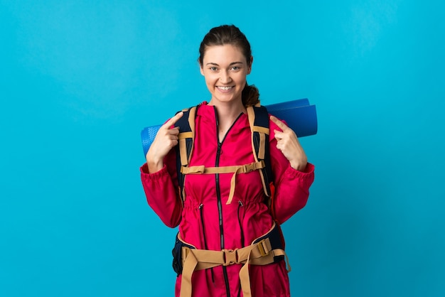 Young mountaineer woman over isolated blue wall giving a thumbs up gesture