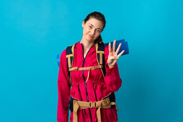 Young mountaineer woman over isolated blue wall happy and counting four with fingers