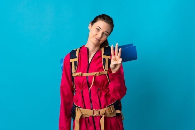 Young mountaineer woman over isolated blue wall happy and counting three with fingers