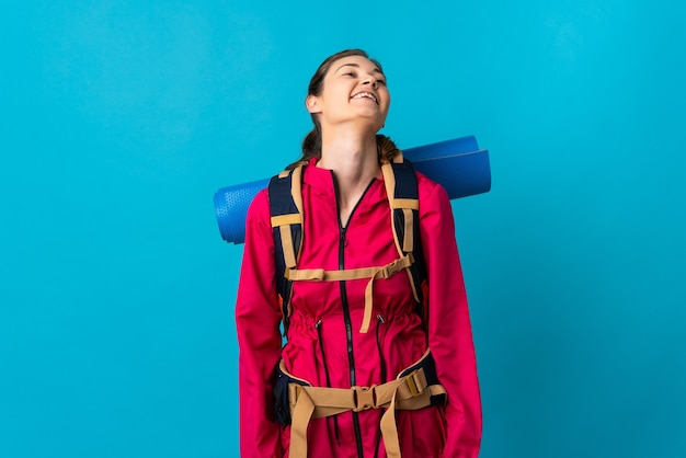 Young mountaineer woman over isolated blue wall laughing
