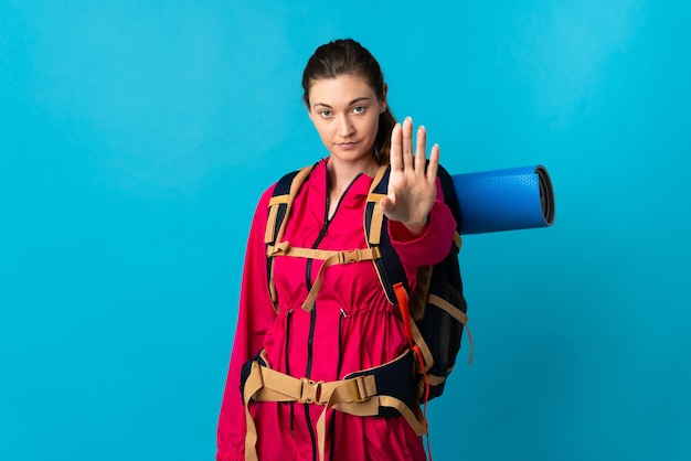 Young mountaineer woman over isolated blue wall making stop gesture