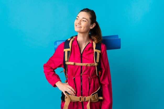 Young mountaineer woman over isolated blue wall thinking an idea while looking up