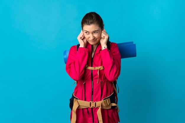 欲求不満と耳を覆っている孤立した青い背景の上の若い登山家の女性