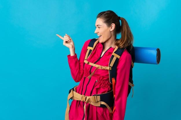 孤立した青い背景の上の若い登山家の女性は、指を横に指し、製品を提示します。