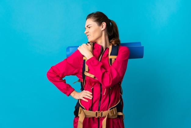努力したために肩の痛みに苦しんでいる孤立した青い背景の上の若い登山家の女性
