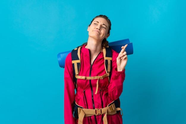 Молодая женщина-альпинист на изолированном синем фоне со скрещенными пальцами и желанием всего наилучшего
