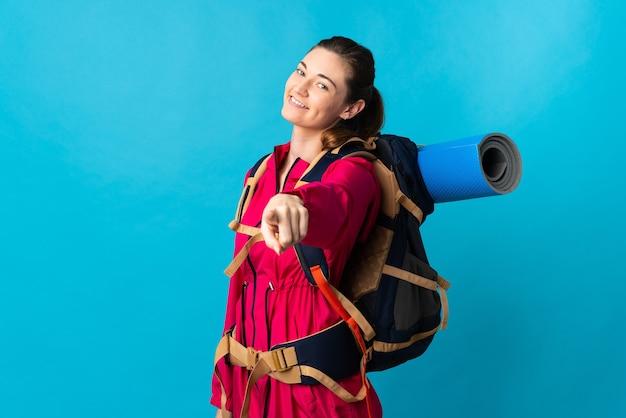 幸せな表情で正面を指す孤立した青い壁の上の若い登山家の女性
