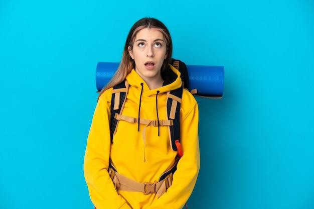 Молодая альпинистка с большим рюкзаком изолирована на синем, глядя вверх и с удивленным выражением лица