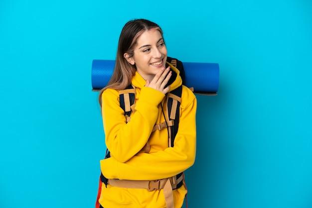 Молодая альпинистка с большим рюкзаком изолирована на синем, глядя вверх, улыбаясь