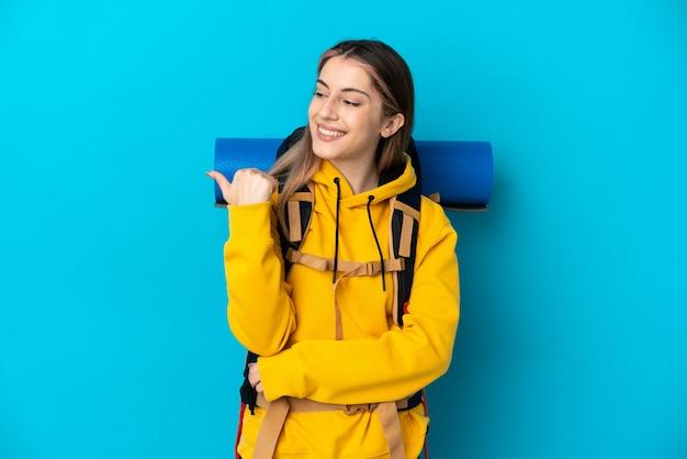 製品を提示する側を指している青い壁に分離された大きなバックパックを持つ若い登山家の女性