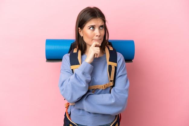 疑問と思考を持っているピンクの背景に分離された大きなバックパックを持つ若い登山家の女性