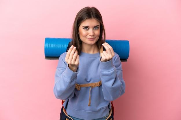 Молодая альпинистка с большим рюкзаком на розовом фоне делает денежный жест