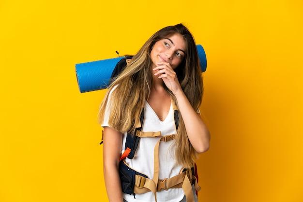 Молодая альпинистка с большим рюкзаком изолирована на желтом и смотрит вверх