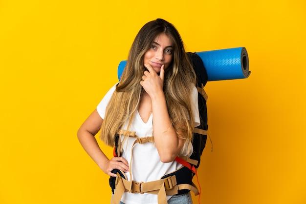 黄色の思考で隔離の大きなバックパックを持つ若い登山家の女性