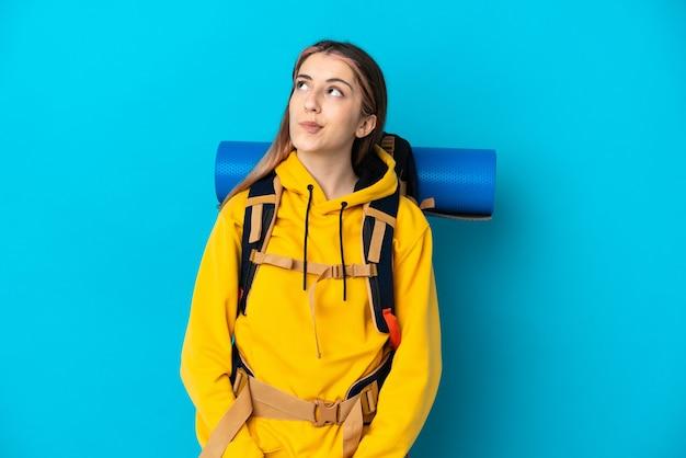 Молодая альпинистка с большим рюкзаком изолирована