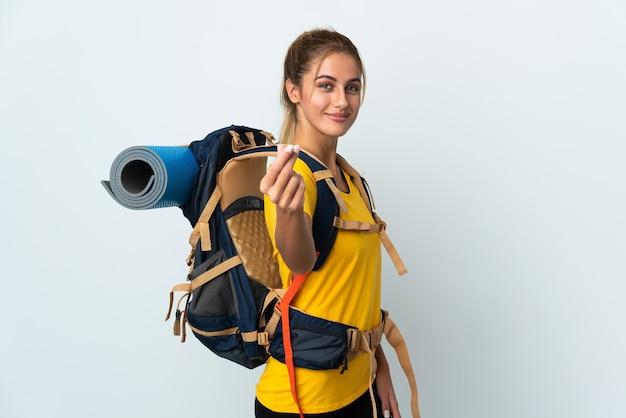 白の大きなバックパックでお金を稼ぐジェスチャーを持つ若い登山家の女性