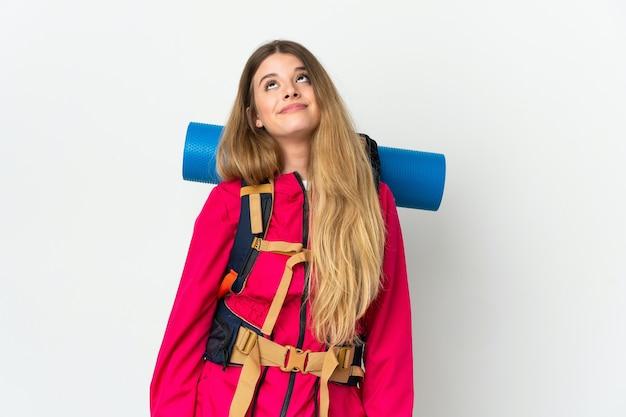 Молодая альпинистка с большим рюкзаком на изолированном фоне и глядя вверх