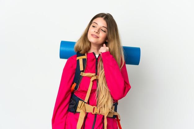 Молодая женщина-альпинист с большим рюкзаком над изолированной стеной и смотрит вверх