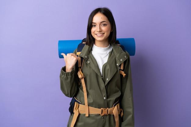 製品を提示する側を指している孤立した壁の上に大きなバックパックを持つ若い登山家の女性