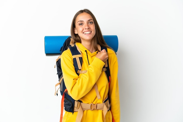 勝利を祝う孤立した白い背景の上の大きなバックパックを持つ若い登山家の女性