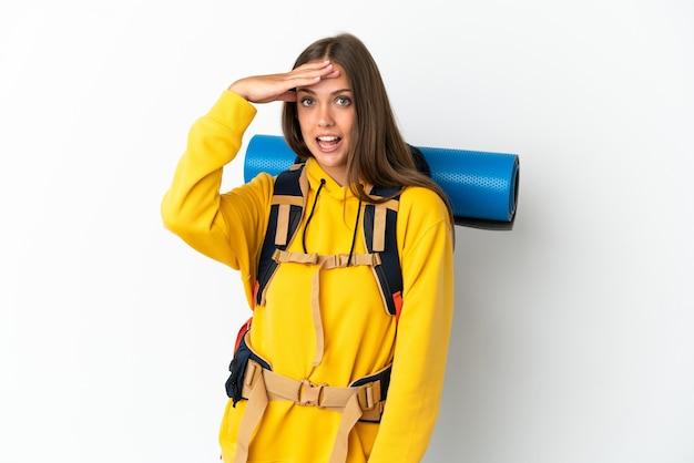 Молодая альпинистка с большим рюкзаком на изолированном белом фоне делает неожиданный жест, глядя в сторону