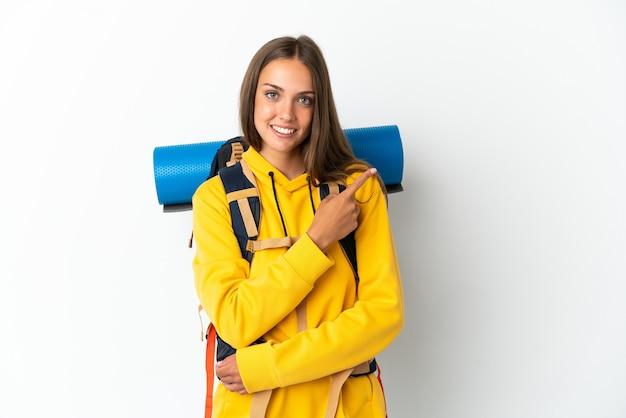 製品を提示する側を指している孤立した白い背景の上に大きなバックパックを持つ若い登山家の女性