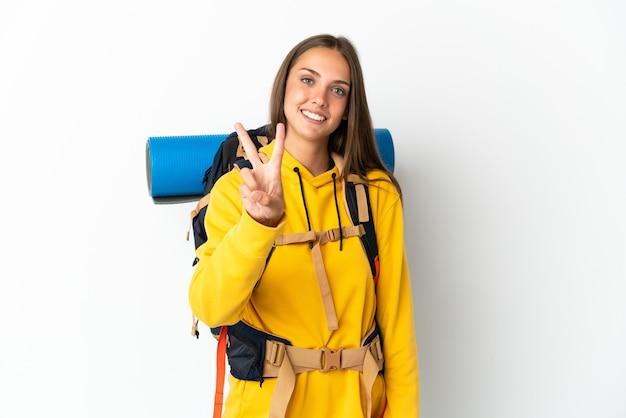 Молодая альпинистка с большим рюкзаком на изолированном белом фоне улыбается и показывает знак победы