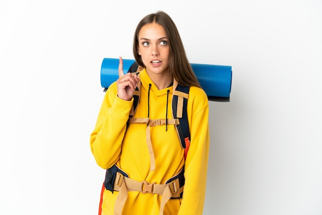 指を上に向けるアイデアを考えて孤立した白い背景の上の大きなバックパックを持つ若い登山家の女性