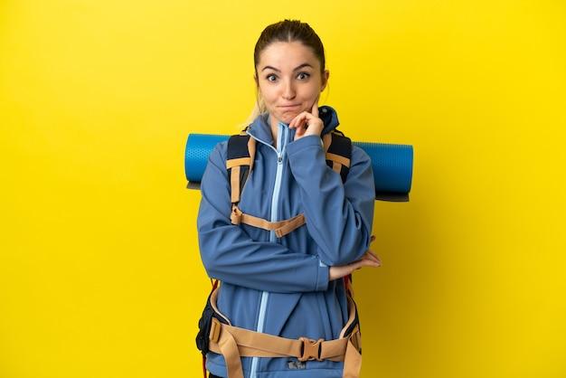 疑いと思考を持っている孤立した黄色の背景の上に大きなバックパックを持つ若い登山家の女性