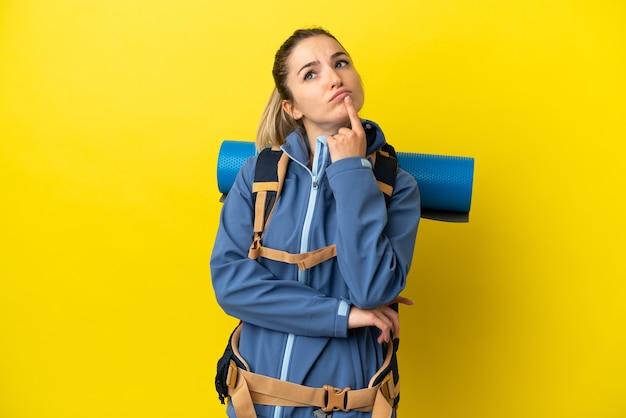 見上げている間疑いを持っている孤立した黄色の背景の上に大きなバックパックを持つ若い登山家の女性