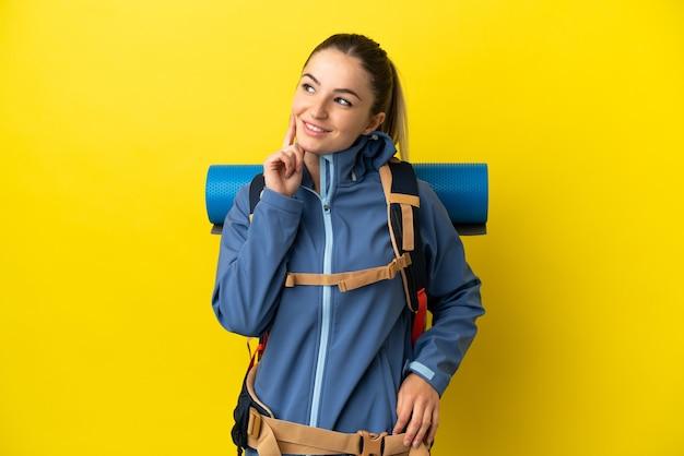 見上げながらアイデアを考えて孤立した黄色の背景に大きなバックパックを持つ若い登山家の女性