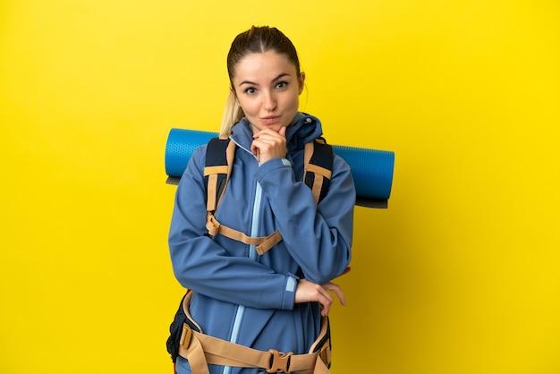 孤立した黄色の背景思考の上の大きなバックパックを持つ若い登山家の女性