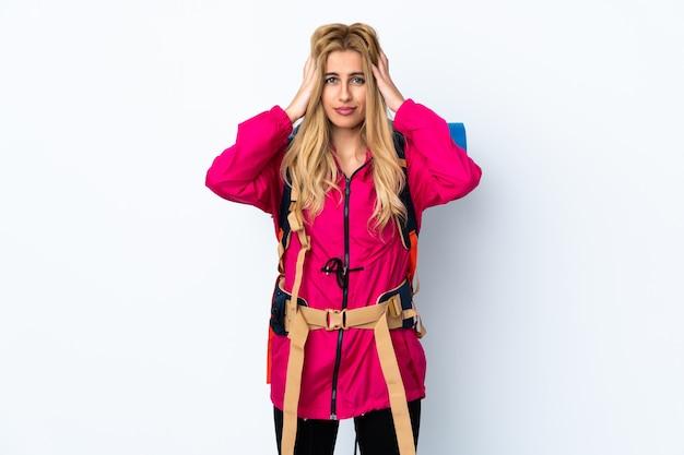 Молодая женщина альпиниста с большим рюкзаком над белой стеной недовольны и разочарованы чем-то. негативное выражение лица