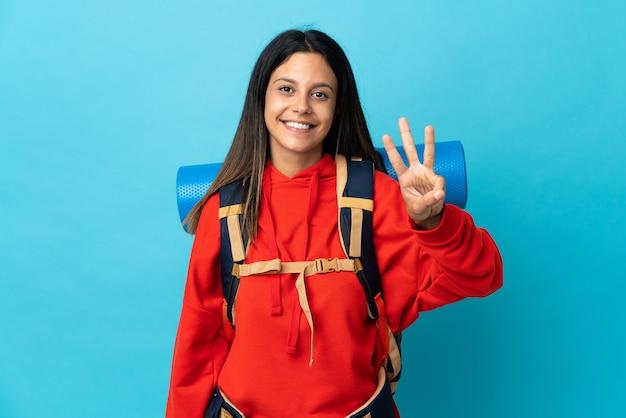 幸せなバックパックと指で3を数える若い登山家の女性