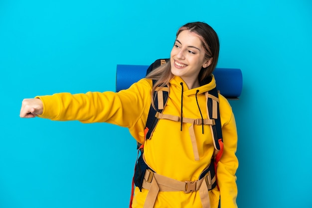 Young mountaineer woman with a big backpack isolated on blue wall giving a thumbs up gesture