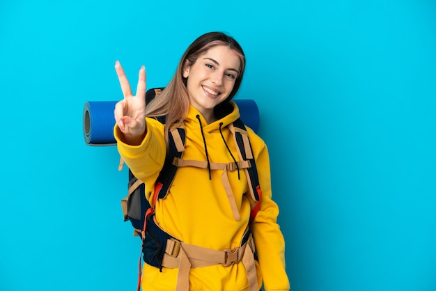 Young mountaineer woman with a big backpack isolated on blue wall smiling and showing victory sign