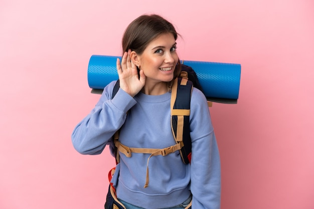 Young mountaineer woman with a big backpack isolated listening to something by putting hand the ear