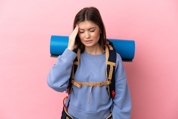 Young mountaineer woman with a big backpack isolated on pink background with headache