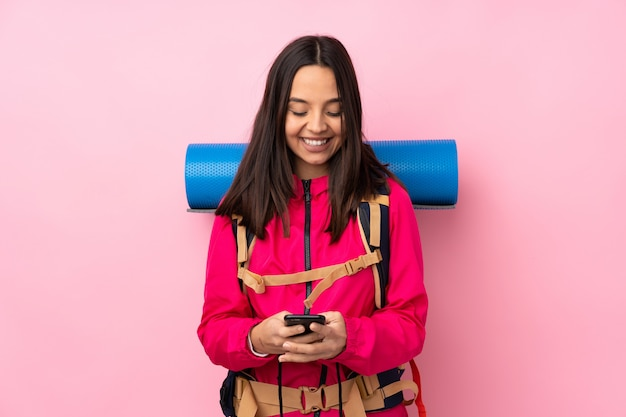 Young mountaineer woman with a big backpack over isolated pink wall sending a message with the mobile