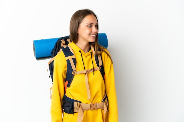 Young mountaineer woman with a big backpack over isolated white background looking to the side and smiling