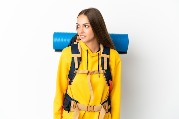 Young mountaineer woman with a big backpack over isolated white background looking side