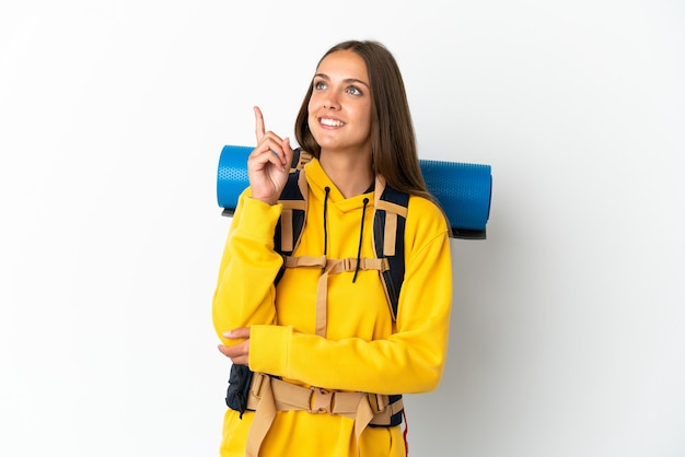 Young mountaineer woman with a big backpack over isolated white background pointing up a great idea