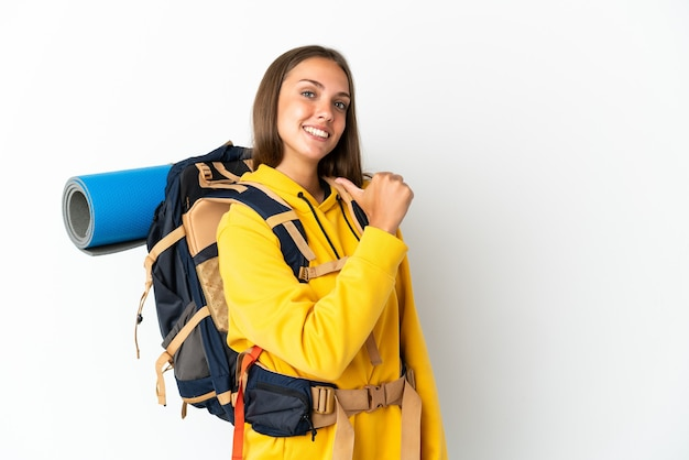 Young mountaineer woman with a big backpack over isolated white background proud and self-satisfied