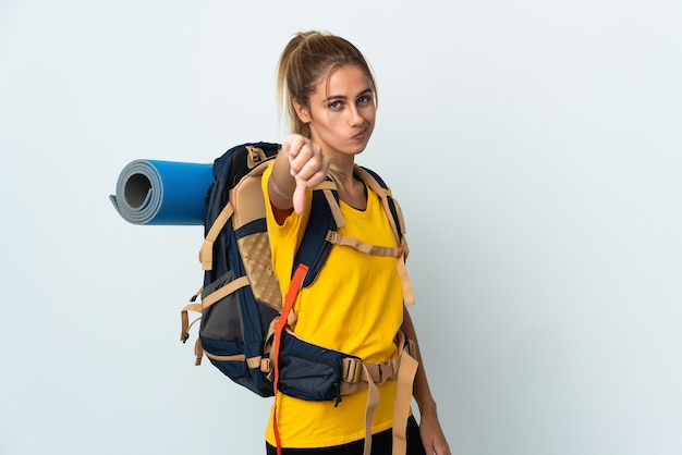 Young mountaineer woman with a big backpack isolated on white space showing thumb down with negative expression