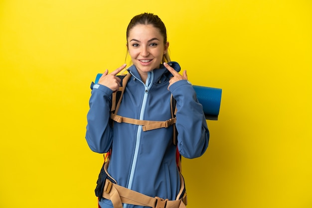 Young mountaineer woman with a big backpack over isolated yellow background giving a thumbs up gesture