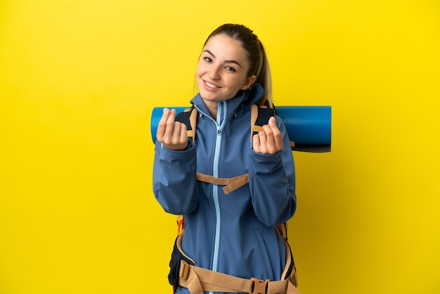 Young mountaineer woman with a big backpack over isolated yellow background making money gesture