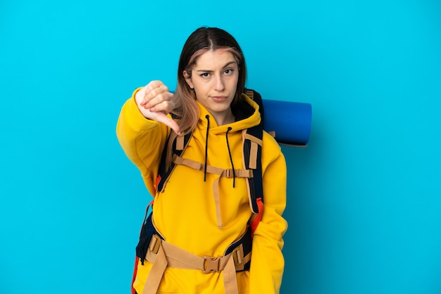 Young mountaineer woman with a big backpack isolated