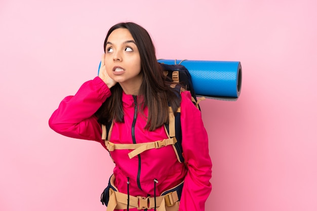 Young mountaineer woman with a big backpack listening to something by putting hand on the ear