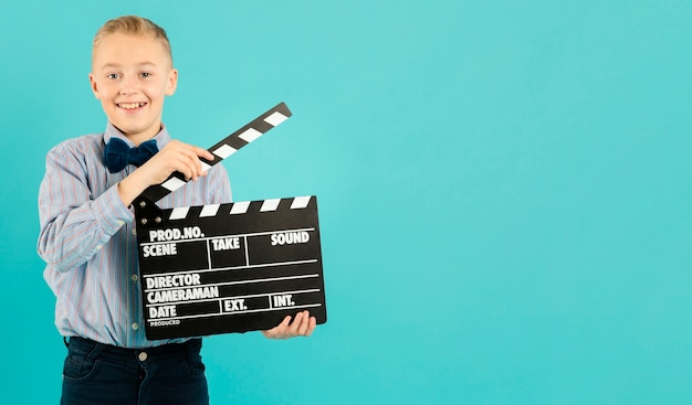 Young movie director holding clapperboard